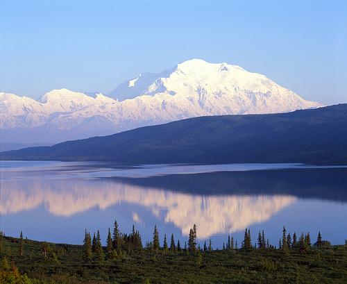 Lumen peittämä vuori ja erämaajärvi Alaskassa.