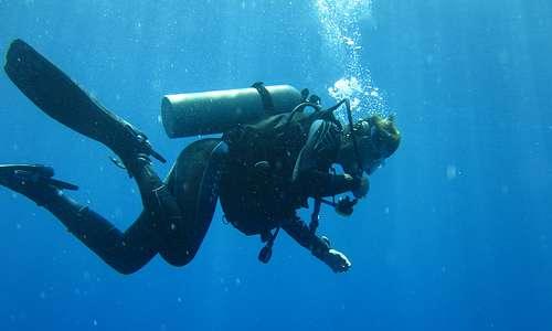 Valokuvassa sukeltaja sinisessä meressä.