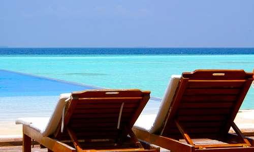 Kaksi rantatuolia Malediiveilla.